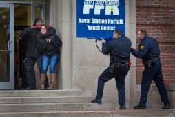 During an active-shooter drill at Norfolk Naval Station, Police Captain Robert Hall pretends to hold Navy Seaman Brandiwyne Torrea hostage as Norfolk police officers William Old, second from right, and Steven Toth, right, engage in a standoff on Wednesday, Feb. 11, 2015. (Photo by Hyunsoo Leo Kim, The Virginian-Pilot)