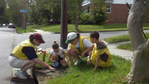 Storm Drain Medallions were placed on drains in Suburban Park and Wards Corner in May 2012 by (from left) Marsha Lockard, Cecilia Fox, C.J. Lockard, and Sebastian Fox.