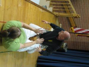 Jen Taylor, an instructor at Norfolk Karate Academy, throws off Master Instructor Bill Odom during a demonstration  at the January 9th, 2012 Suburban Acres Civic League Meeting.